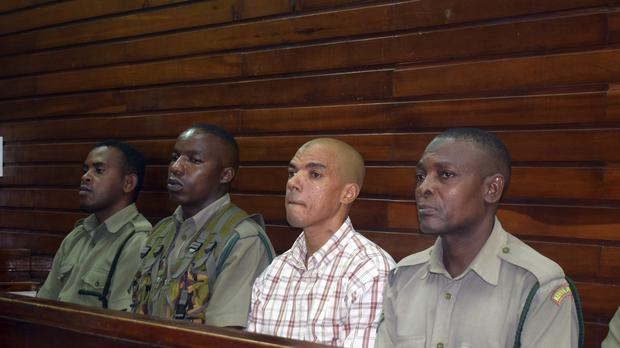 Guarded by heavy security, Jermaine Grant, second right, sits in a Mombasa court (AP)