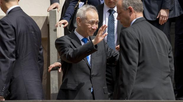 Chinese Vice Premier Liu He waves to members of the media as he departs the Office of the United States Trade Representative in Washington (Andrew Harnik/AP)