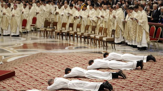 Priests lie face down on the floor during an ordination ceremony presided over by Pope Francis in St Peter's Basilica (Alessandra Tarantino/AP)