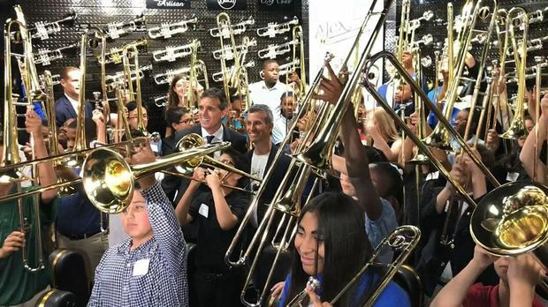 Fifty students surround Max Schachter and Fred Schiff to blast a B-flat on their new Alex Tribute Trombones (Wayne K. Roustan/South Florida Sun-Sentinel/AP)