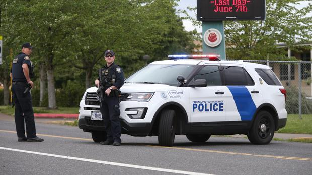 Police are positioned outside Parkrose High School (Dave Killen/AP)
