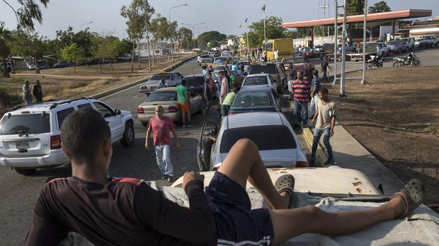 People line the street with their vehicles as they wait to fill up at a fuel station in Cabimas, Venezuela (Rodrigo Abd/AP)