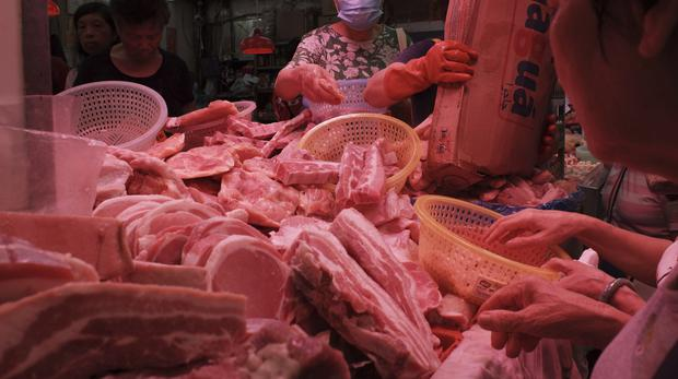 Customers buy frozen pork at a local market in Hong Kong (Kin Cheung/PA)