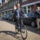 Mark Rutte leaves on his bicycle after voting in the European elections (Phil Nijhuis/AP)