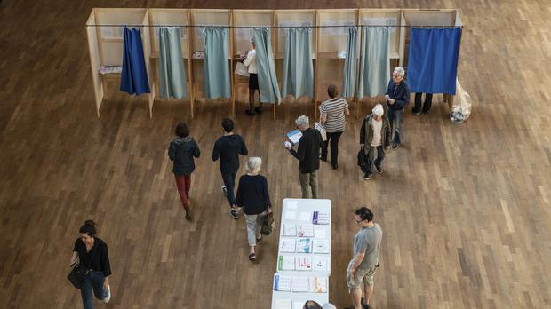 Voters pick up ballots before voting in Lyon, central France (Laurent Cipriani/AP)