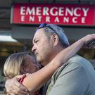 Sarah Haynes embraces John Eller, father of Amanda Eller, outside a hospital in Maui (Bryan Berkowitz/Honolulu Star-Advertiser via AP)