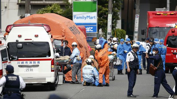 Rescuers work at the scene of the attack in Kawasaki (Kyodo News via AP)