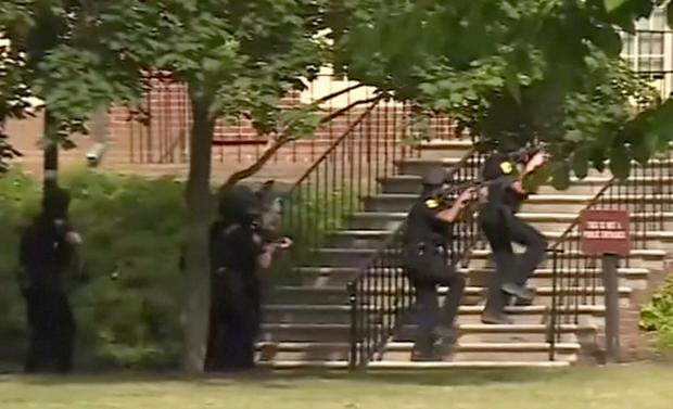 LIVE SHOOTER: Police storm the Virginia Beach Municipal Centre yesterday where a disgruntled ex-employee killed 12 people in a mass shooting. Photo: Reuters