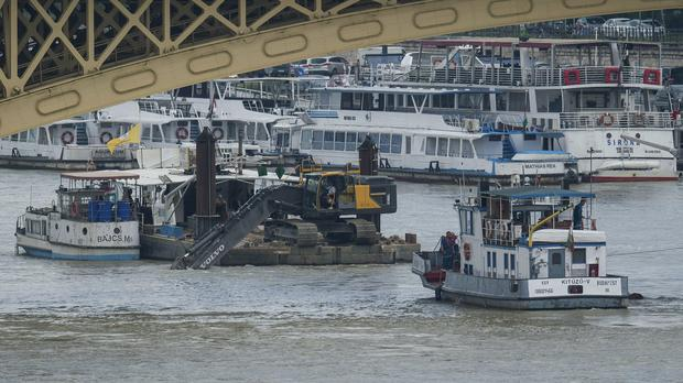 A power shovel fixed on a pontoon at work at the scene of the collision on the River Danube (Zoltan Balogh/MTI via AP)