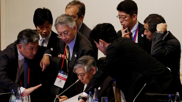 Haruhiko Kuroda, governor of the Bank of Japan, is surrounded by his delegates during the G20 meeting (Kim Kyung-hoon/Pool/AP)