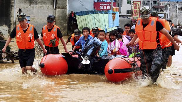Chinese paramilitary policemen evacuate residents trapped by flooding in Heyuan in southern China's Guangdong province (AP)