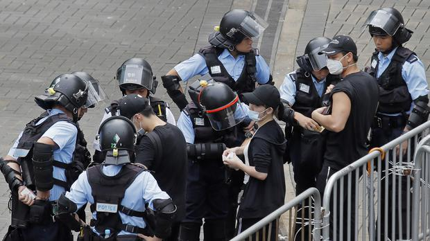 Riot police check the bags of protesters outside the Legislative Council in Hong Kong (Kin Cheung/AP)