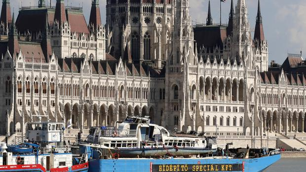 A barge carries a sightseeing boat past the house of parliament on the Danube river after it was lifted from riverbed in Budapest, Hungary (Darko Bandic/AP)