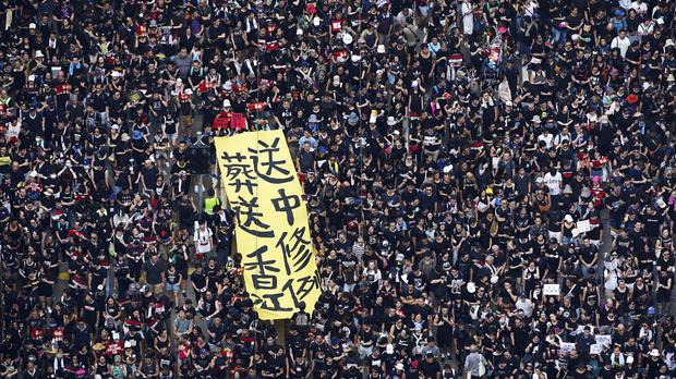 Tens of thousands of protesters carry posters and banners as they march through the streets in Hong Kong (Apple Daily via AP)