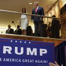 Donald Trump, accompanied by his wife Melania Trump, is applauded by his daughter Ivanka Trump, right as he is introduced before his 2015 announcement that he will run for president in the lobby of Trump Tower in New York (Richard Drew/AP)