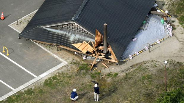 The roof of the wooden sumo building falls on the site of the Oizumi Elementary School in Tsuruoka, Yamagata prefecture (Kyodo via AP)