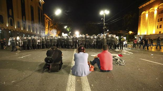 Three opposition demonstrators sit in front of a police line at the Georgian Parliament (Zurab Tsertsvadze/AP)