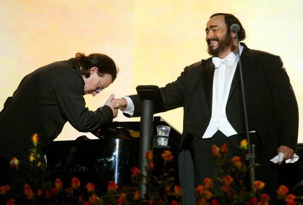 Bono bows before Italian tenor Luciano Pavarotti (R) at the end of his performance at the 'Pavarotti & Friends 2003' concert in Modena, Italy, May 27, 2003