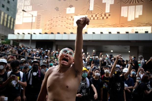 People power: A protester holds eggs to throw at police as thousands surround the police headquarter in Hong Kong. Photo: Paula Bronstein