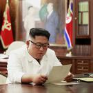 North Korean leader Kim Jong Un reads a letter from US President Donald Trump (Korean Central News Agency/Korea News Service/AP)