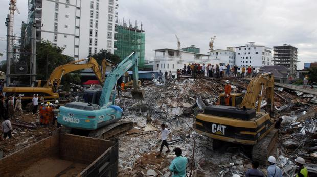 Rescuers try to remove rubble at the site of a collapsed building in Preah Sihanouk province, Cambodia (Heng Sinith/AP)