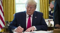 President Donald Trump signs an executive order to increase sanctions on Iran, in the Oval Office of the White House (Alex Brandon/AP)