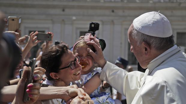 Pope Francis blesses a child during his weekly general audience (Gregorio Borgia/AP)
