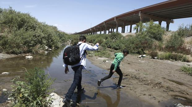 People cross the Rio Grande into the United States to turn themselves over to authorities and ask for asylum (Christian Torres/AP)