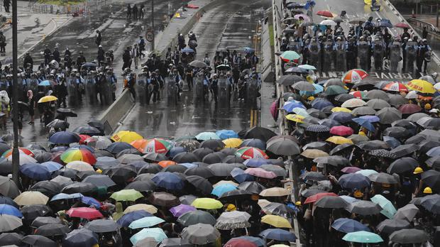 Protesters holding umbrellas face police officers in anti-riot gear in Hong Kong (Kin Cheung/AP)
