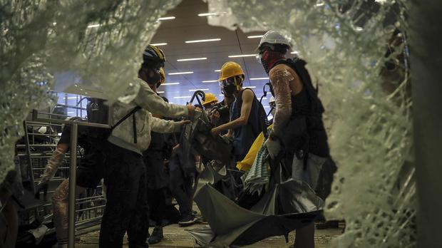 Protesters collect umbrellas near the damaged glass of the Legislative Council (Kin Cheung/AP)