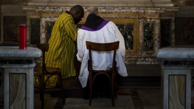 A Roman Catholic priest, back to camera, listens to a man's confession (Emilio Morenatti/AP)