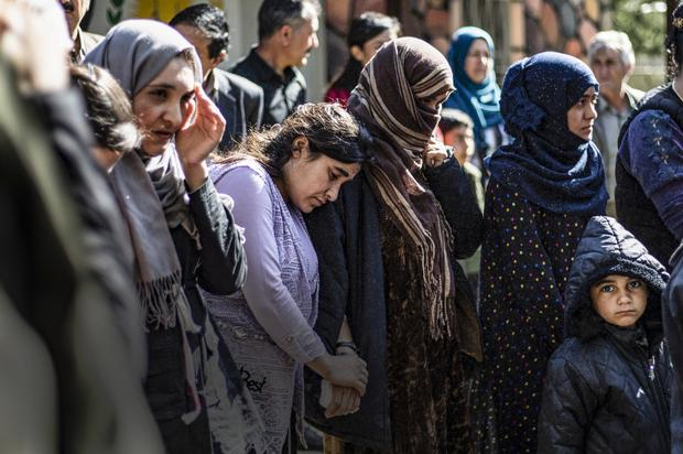 Iraqi Yazidi women and children rescued from Isil wait to board buses bound for Sinjar in Iraq's Yazidi heartland in April of this year