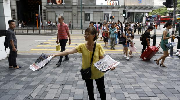 A woman distributes newspapers in a shopping district popular with mainland Chinese tourists in Hong Kong (AP Photo/Andy Wong)