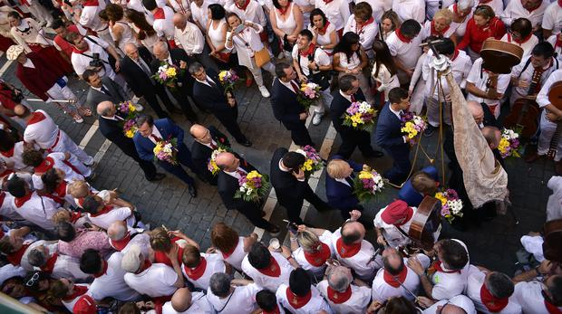 People dressed in white and red clothes take part in a procession at the San Fermin Festival (Alvaro Barrientos/AP)
