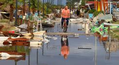 Force of nature: A man cycles through the debris after the storm hit Nea Plagia village, Halkidiki. Photo: AP