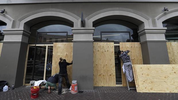 Workers board up windows in the French Quarter of New Orleans (David J Phillip/AP)