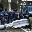 Police with a missile seized at an airport hangar near Pavia, northern Italy (Tino Romano/ANSA via AP)