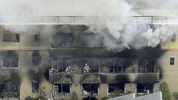Firefighters work as smoke billows from a three-story building of Kyoto Animation in a Japan (Kyodo News via AP)