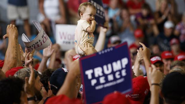 A baby is held high in the audience as President Donald Trump speaks at a campaign rally at Williams Arena in Greenville, North Carolina (AP/Carolyn Kaster)