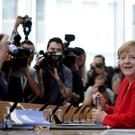 German Chancellor Angela Merkel smiles as she arrives for her annual summer press conference in Berlin (Michael Sohn/AP)