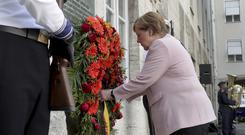 German Chancellor Angela Merkel adjusts a wreath during a memorial event at the Defence Ministry in Berlin (Michael Sohn/AP)