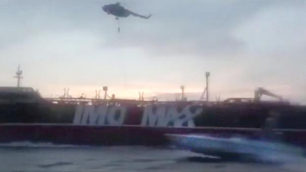 CRISIS: Iranian Revolutionary Guards rappel onto the deck of the Stena Impero, as one of their motorboats flashes by