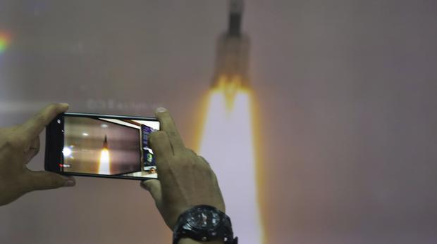 A man at New Delhi's Nehru Planetarium takes pictures of a web cast of the lift off (Manish Swarup/AP)
