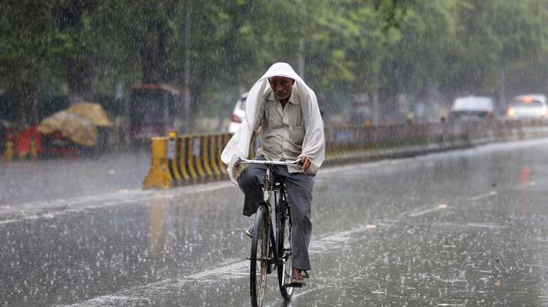 A man covers himself with a scarf and rides his bicycle in the rain in Prayagraj (Rajesh Kumar Singh/AP)