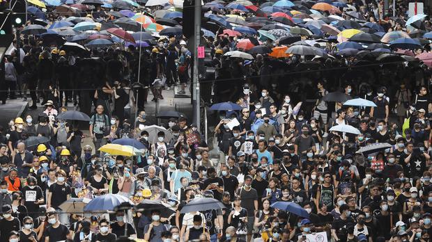 A sea of black-shirted protesters carry placards during a protest march in Hong Kong (Vincent Yu/AP)