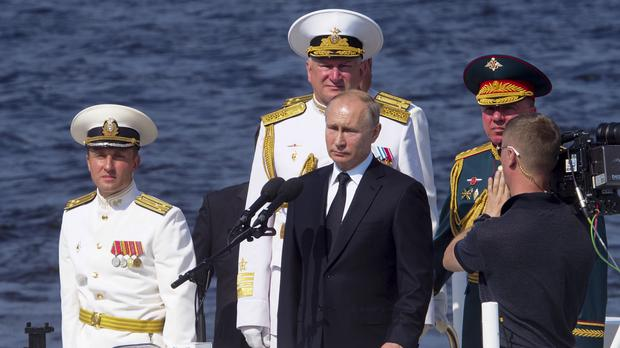 Russian President Vladimir Putin, centre, and Commander-in-Chief of the Russian Navy Nikolai Yevmenov, behind Mr Putin, arrive to attend the military parade during the Navy Day celebration in St.Petersburg (Dmitri Lovetsky/Pool/AP)