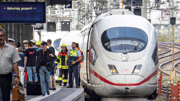 Firefighters and police officers stay next to an ICE highspeed train at the main station in Frankfurt, Germany (Frank Rumpenhorst/AP)