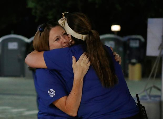 Shock: Two festival volunteers embrace after the attack. Photo: AP