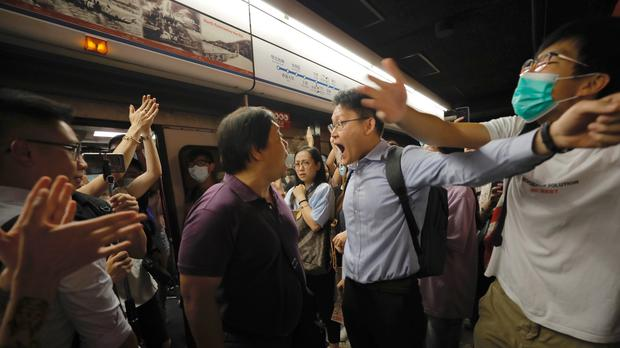 Passengers argue with protesters who disrupted a subway line in Hong Kong by blocking the doors on trains, preventing them from leaving the stations (Vincent Yu/AP)