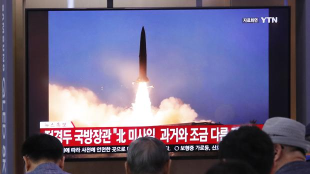 People in Seoul watch a TV showing a file image of a North Korea missile launch (Ahn Young-joon/AP)
